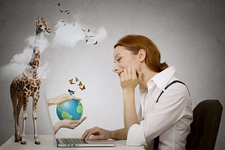 Happy dreaming woman sitting in front of computer, hands with earth coming from laptop screen, giraffe standing on desk. photo