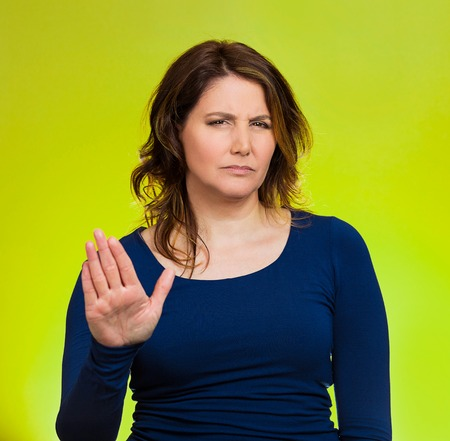 Closeup portrait middle aged, annoyed woman with bad attitude, giving talk to hand gesture with palm outward, isolated green background.