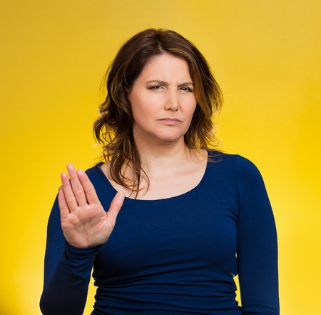 cranky: Closeup portrait middle aged, annoyed woman with bad attitude, giving talk to hand gesture with palm outward, isolated yellow background.
