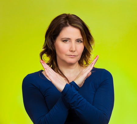 non verbal: Portrait angry middle aged woman showing X gesture asking to stop talking, cut it out, dont go there, isolated green background.