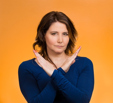 admonish: Portrait angry middle aged woman showing X gesture asking to stop talking, cut it out, dont go there, isolated orange background.
