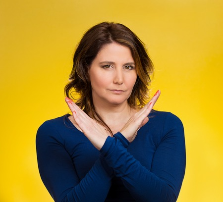 admonish: Portrait angry middle aged woman showing X gesture asking to stop talking, cut it out, dont go there, isolated yellow background.