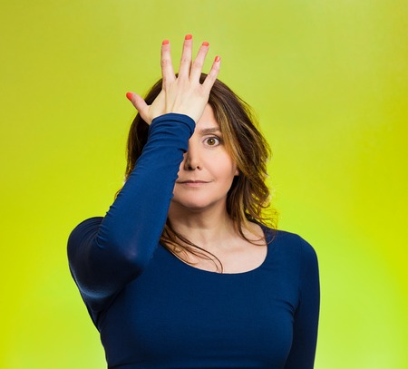 Portrait middle aged woman realizes mistake, slapping hand on head to say duh, isolated green background.  Stock Photo