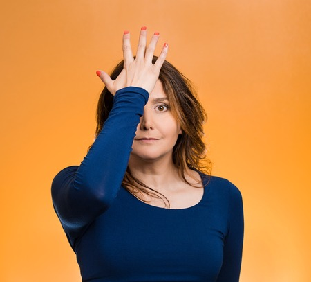 duh: Portrait middle aged woman realizes mistake, slapping hand on head to say duh, isolated  orange background.