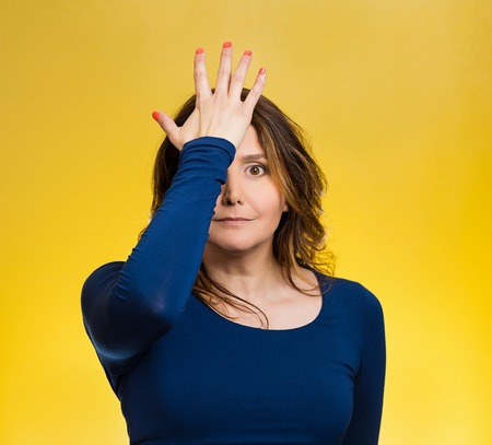 duh: Portrait middle aged woman realizes mistake, slapping hand on head to say duh, isolated yellow background. Stock Photo