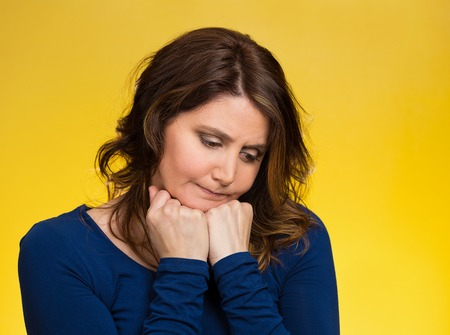 bothered: Closeup portrait unhappy middle age woman, head on hand, looking down bothered by mistake having day isolated yellow background. Stock Photo