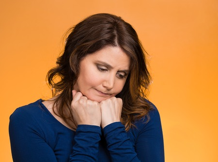 bothered: Closeup portrait unhappy middle age woman, head on hand, looking down bothered by mistake having day isolated orange background.  Stock Photo