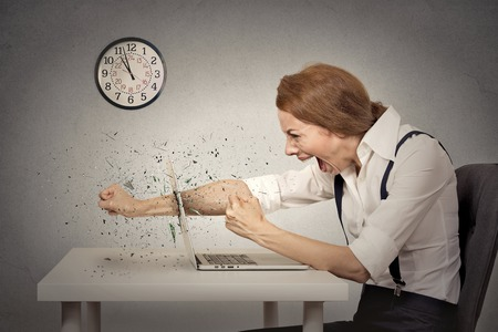 anger management: Angry, furious businesswoman throws a punch into computer, screaming. Negative human emotions, facial expressions, feelings, aggression, anger management issues