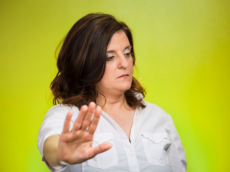 Offended. Portrait middle age grumpy woman with bad attitude giving talk to my hand gesture with palm outward, isolated green background. Negative emotions, facial expression feelings, body language