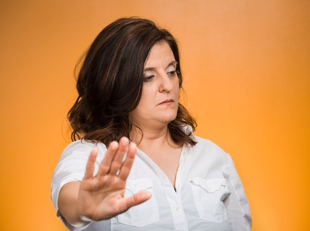 talk to the hand: Offended. Portrait middle age grumpy woman with bad attitude giving talk to my hand gesture with palm outward, isolated orange background. Negative emotions, facial expression feelings, body language Stock Photo
