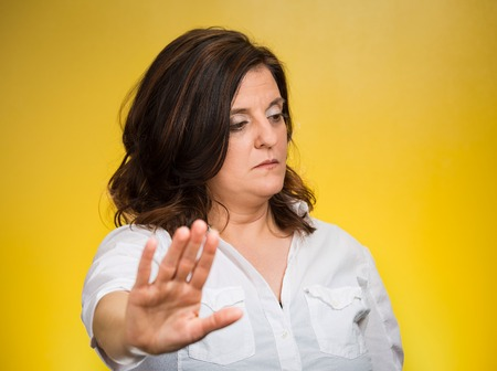 cranky: Offended. Portrait middle age grumpy woman with bad attitude giving talk to my hand gesture with palm outward, isolated yellow background. Negative emotions, facial expression feelings, body language