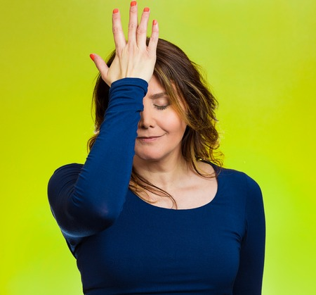 duh: Portrait sad middle aged woman realizes mistake, regrets, slapping hand on head to say duh, isolated green background. Negative emotions, facial expression, feelings, body language, reaction