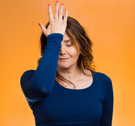 duh: Portrait sad middle aged woman realizes mistake, regrets, slapping hand on head to say duh, isolated orange background. Negative emotions, facial expression, feelings, body language, reaction