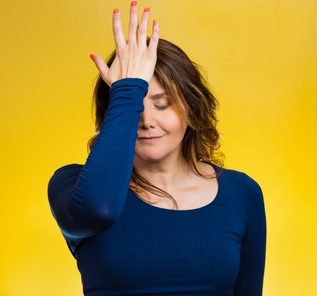 Portrait sad middle aged woman realizes mistake, regrets, slapping hand on head to say duh, isolated yellow background. Negative emotions, facial expression, feelings, body language, reaction