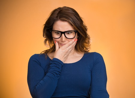 Awkward situation. Portrait embarrassed woman anxiously thinking how to get out of this, isolated orange background. Human face expressions, emotions, feelings, reaction, life perception