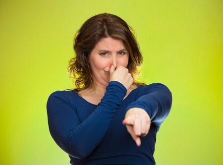 unpleasant: Portrait unhappy woman pinches nose, looks displeased, pointing at you with finger something, you stink, bad smell isolated green background. Human facial expressions, emotions, feelings, reaction Stock Photo