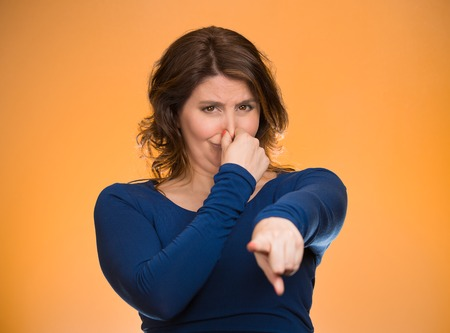 intolerable: Portrait unhappy woman pinches nose, looks displeased, pointing at you with finger something, you stink, bad smell isolated orange background. Human facial expressions, emotions, feelings, reaction