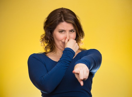 fetid: Portrait unhappy woman pinches nose, looks displeased, pointing at you with finger something, you stink, bad smell isolated yellow background. Human facial expressions, emotions, feelings, reaction Stock Photo