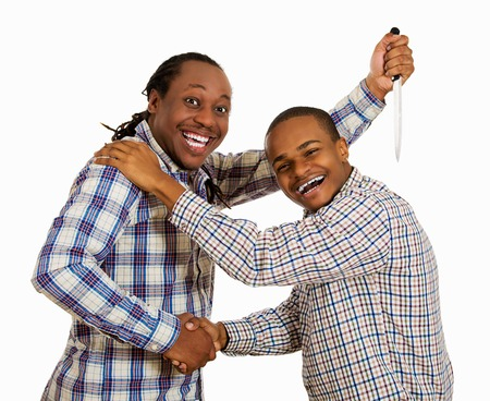 Fake friend backstabbing concept. Portrait hypocrite, crafty man gives handshake to a guy at same time trying to stab him in back with knife isolated white background. Human emotion expression feeling Standard-Bild