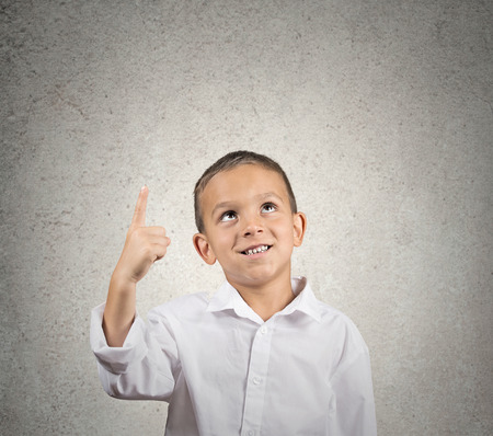 Portrait boy pointing with index finger up, looking up at copy space isolated grey wall background. positive face expressions photo