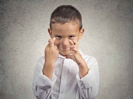 crossing fingers: Child crossing fingers. Young man making wish, hopeful, looking up isolated grey wall background. Human face expressions, emotions, feelings, body language, signs, symbols Stock Photo