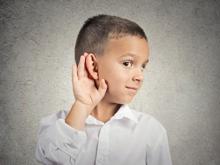 chitchat: Curious man, boy, listens. Closeup portrait child hearing something, parents talk, hand to ear gesture isolated grey wall background. Human face expression, emotion, body language, life perception