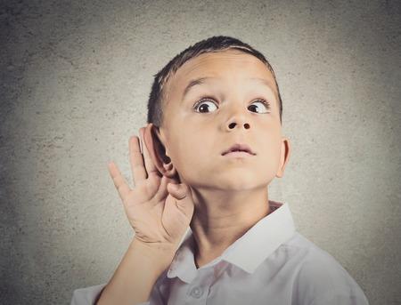 Curieux homme, garçon, écoute. Gros plan portrait enfant quelque chose de l'audience, les parents parlent à la main à l'oreille geste isolé gris mur arrière-plan. L'expression humaine de visage, l'émotion, le langage du corps, la perception de la vie