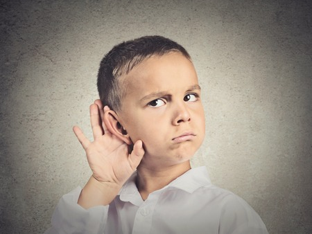 eavesdropping: Curious man, boy, listens. Closeup portrait child hearing something, parents talk, hand to ear gesture isolated grey wall background. Human face expression, emotion, body language, life perception