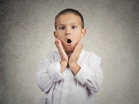 Wow, surprise. Portrait surprised child, boy with stunned face expression, disbelief, blown away by what he see, cant belief it is for real, isolated grey wall background. Human emotions, reaction photo