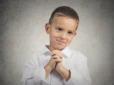 Closeup portrait boy, young man gesturing with clasped hands, pretty please with sugar on top, isolated grey background. Positive emotions, facial expressions, feelings, signs symbols, body language