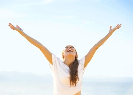 Frau lächelnd Arme bis zu den blauen Himmel, die Freiheit zu feiern. Positive menschlichen Emotionen, Gesicht Ausdruck Gefühl Leben Wahrnehmung Erfolg, Ruhe Konzept. Free Happy Mädchen am Strand die Natur genießen