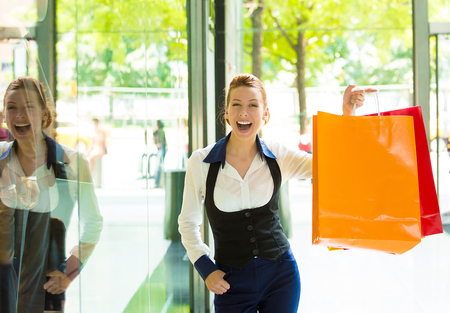 Portrait Shopping woman in New York City. Beautiful model happy, smiling summer shopper holding shopping bags standing in front of window display. Positive human emotions, facial expressions, feelings photo