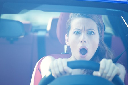 Dear in headlights. Fright face woman driving car, wide open mouth eyes, strongly squeezing wheel, front window view. Negative human face expressions, emotions, reaction. Road trip risk danger concept