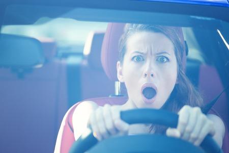 Liebe in Scheinwerfern. Fright Gesicht Frau fahrenden Auto, weit geöffneten Mund Augen, stark drückte Rad, vorne Fensteransicht. Negative menschliche Gesichtsausdrücke, Emotionen, Reaktion. Road trip Risiko Gefahr Konzept