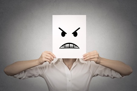 bad attitude: businesswoman covering her face with angry mask isolated grey wall background. Negative emotions, feelings, expressions, body language