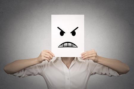 lenguaje corporal: empresaria que cubre su rostro con máscara enojada aisló el fondo gris de la pared. Emociones negativas, sentimientos, expresiones, lenguaje corporal
