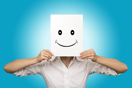 Woman showing happy emotion holding covering front of face with smiling paper mask isolated on blue background. Human facial expressions, fake identity, unknown, behind the scene concept