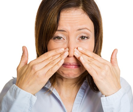 Closeup portrait middle aged woman covers, pinches her nose with hands looks with disgust, something stinks, bad smell, situation, isolated white background. Human face expressions, body language