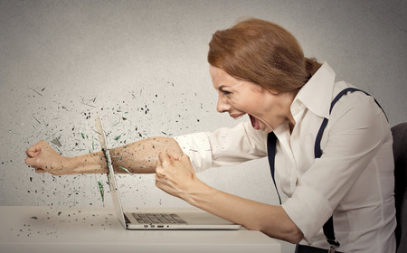 Angry, furious businesswoman throws a punch into computer, screaming. Negative human emotions, facial expressions, feelings, aggression, anger management issues photo