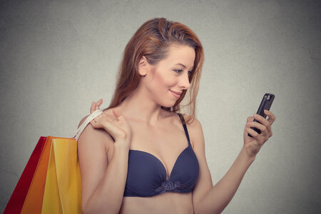 gat: Time to shop. Beautiful woman holding shopping bags, looking gat her smart phone, browsing on-line sale, deals, isolated grey wall background. Positive face expressions, emotions, feelings