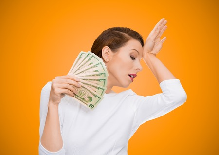 Im rich spoiled drama queen. Portrait attractive woman model holding dollar banknotes lie fan, feels tired melancholic detached from reality, isolated orange background. Human face expression emotion