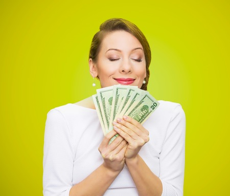 miser: Hungry for money. Portrait, greedy executive, CEO, boss, corporate employee, holding, smelling dollar banknotes tightly, isolated green background. Human emotion facial expression life perception