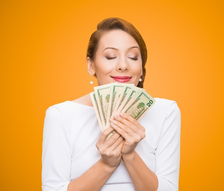 tightly: Hungry for money. Portrait, greedy executive, CEO, boss, corporate employee, holding, smelling dollar banknotes tightly, isolated orange background. Human emotion facial expression life perception