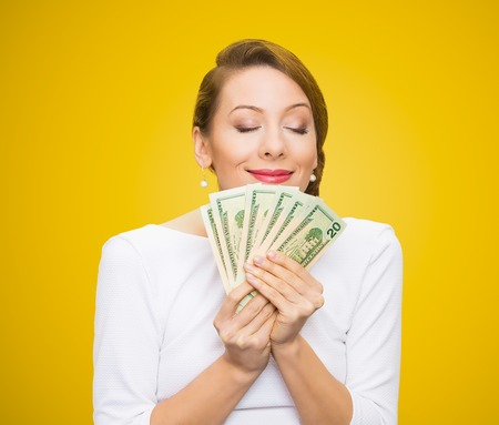 stingy: Hungry for money. Portrait, greedy executive, CEO, boss, corporate employee, holding, smelling dollar banknotes tightly, isolated yellow background. Human emotion facial expression life perception Stock Photo