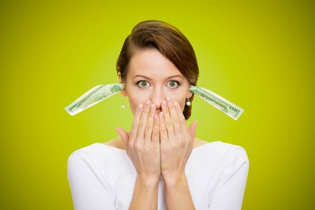 under paid: Corruption. It will keep me quiet. Bribery concept in politics, business, diplomacy. Corporate businesswoman plugs her ears with dollar banknotes, bills, covers her mouth, isolated green background