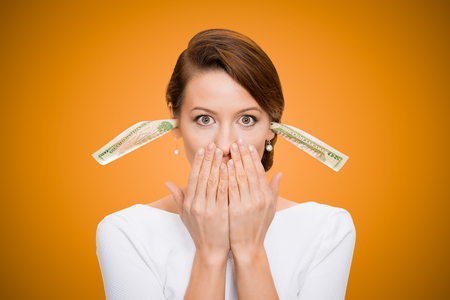 wrongful: Corruption. It will keep me quiet. Bribery concept in politics, business, diplomacy. Corporate businesswoman plugs her ears with dollar banknotes, bills, covers her mouth, isolated orange background  Stock Photo