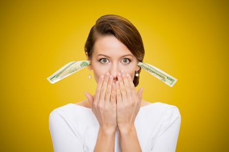 wrongful: Corruption. It will keep me quiet. Bribery concept in politics, business, diplomacy. Corporate businesswoman plugs her ears with dollar banknotes, bills, covers her mouth, isolated yellow background  Stock Photo