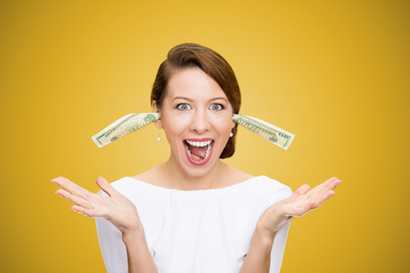 wrongful: Excited happy woman ears plugged with dollar banknotes