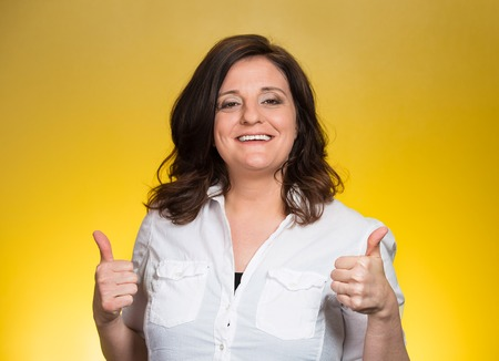 Happy smiling businesswoman with thumbs up gesture, isolated on yellow background. Positive human emotions, facial expressions, feelings, body language, signs, symbols