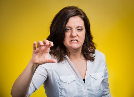 anger management: Closeup irritated stressed unhappy angry middle aged woman threatening someone with her claws nails isolated yellow background. Negative human emotion facial expression feeling reaction body language Stock Photo